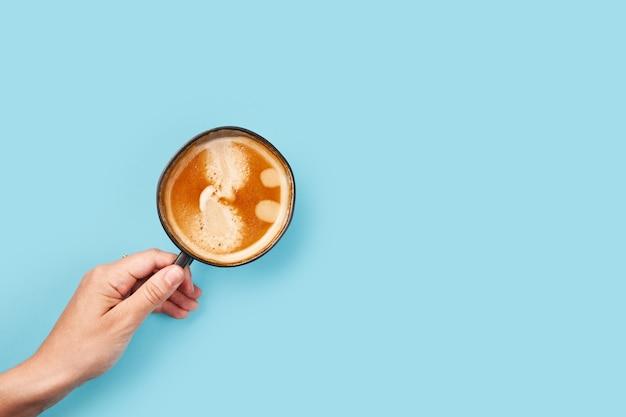 青色の背景にカップのコーヒーの平面図です。朝のコーヒータイム。高品質の写真