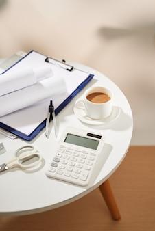 흰색 테이블에 있는 커피 공책 빈 페이지, 계산기, 가위의 상위 뷰