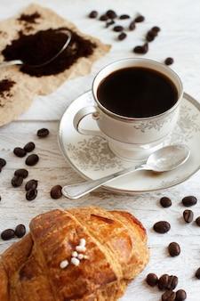 素朴な白い木の上にクロワッサンとコーヒーの上面図