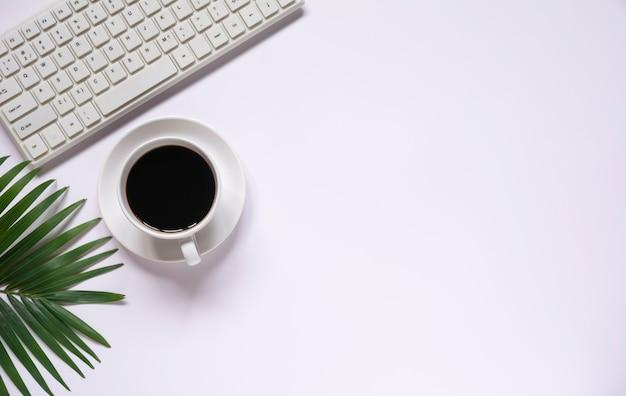 白い背景と挿入テキスト用のコピースペースに他の消耗品とキーボードとコーヒーの上面図。