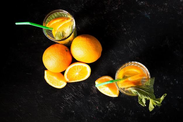 짙은 빈티지 나무 배경에 있는 유기농 과일 옆 안경에 있는 차가운 맛있는 오렌지에이드의 최고 전망
