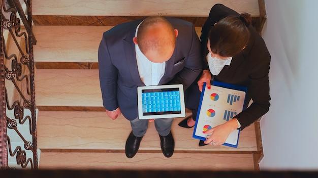 タブレットを使用して企業の会社の建物の階段に立っている困難な締め切りの財務プロジェクトでコワーキングを支援する同僚の上面図。金融の職場を歩いているビジネスマンのグループ