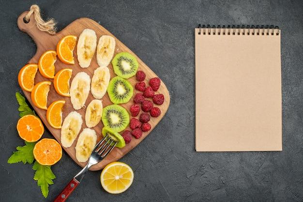 木製のまな板と暗い表面のノートブックに刻んだ新鮮な果物のコレクションの上面図