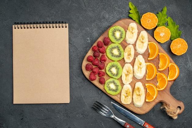 木製のまな板と黒いテーブルの上のスパイラルノートに刻んだ新鮮な果物のコレクションの上面図