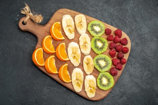垂直方向のビューで黒いテーブルの上の木製のまな板に刻んだ新鮮な果物のコレクションの上面図
