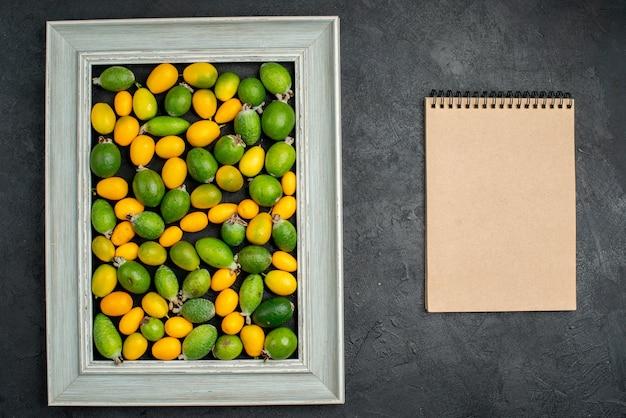 暗いテーブルの上の額縁とスパイラルノートの柑橘系の果物のコレクションの上面図
