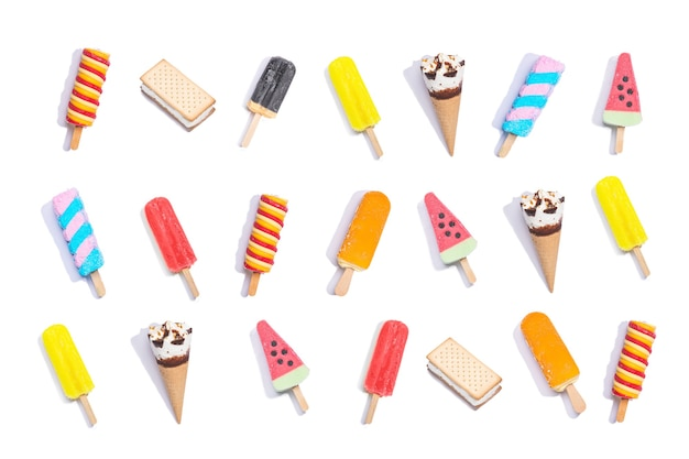 白い背景の上のカラフルなアイスクリームのさまざまなアイスキャンディーのコレクションの上面図。フラットレイ構成。