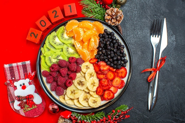 Вид сверху коллекции свежих фруктов на тарелке украшения аксессуары еловые ветки и цифры рождественский носок на красной салфетке и набор столовых приборов на черном фоне