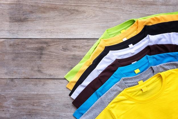 Вид сверху цветной футболки на фоне серой древесины