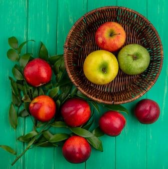Вид сверху цветных яблок в корзине с персиками на ветвях листьев на зеленой поверхности