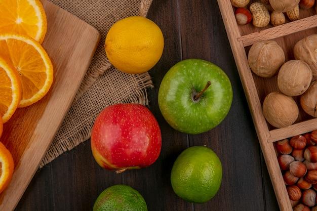 レモンブラックカラントと木の表面にナッツのボード上のスライスされたオレンジ色のリンゴの平面図
