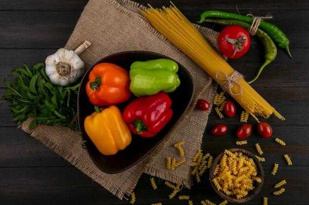 Вид сверху цветного болгарского перца в миске с сырыми спагетти и пастой, перцем чили, чесноком и помидорами на деревянной поверхности