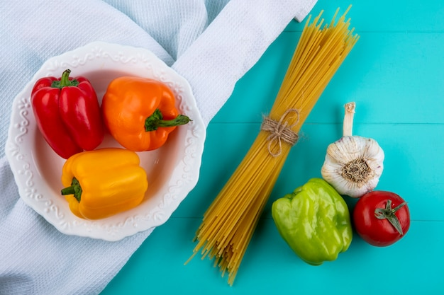 Вид сверху цветного болгарского перца в белой тарелке на белом полотенце с сырыми спагетти, помидорами и чесноком
