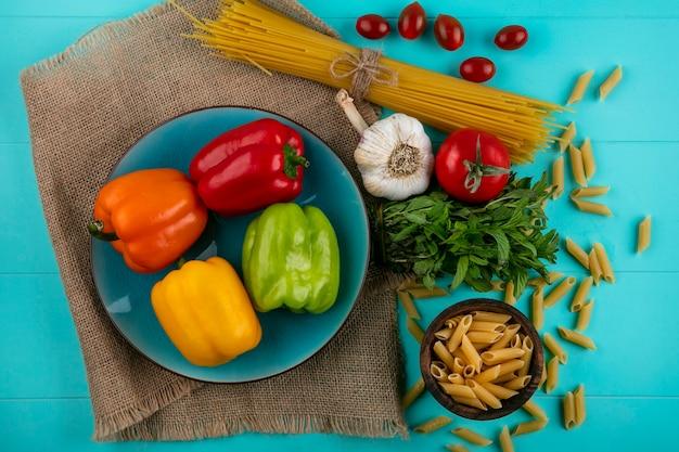 Вид сверху цветного сладкого перца на синей тарелке с сырой пастой и спагетти, помидорами черри и чесноком на бирюзовой поверхности