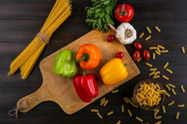 Вид сверху цветного сладкого перца на разделочной доске с мытым чесноком и сырыми спагетти на деревянной поверхности