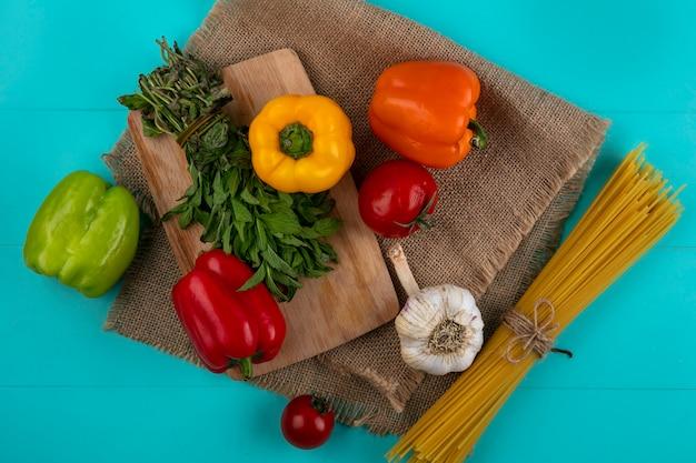 Вид сверху цветного сладкого перца на разделочной доске с сырыми спагетти с мятой и чесноком на бирюзовой поверхности