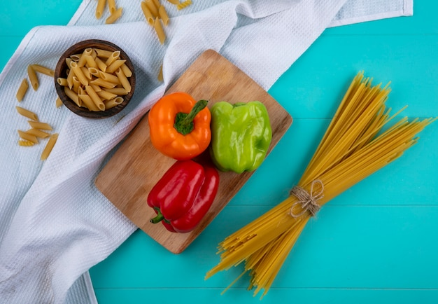 Вид сверху цветного сладкого перца на разделочной доске с сырыми спагетти и пастой на бирюзовой поверхности