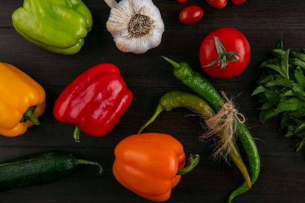 Вид сверху цветного болгарского перца с перцем чили, чесноком, кучей мяты и помидорами на деревянной поверхности
