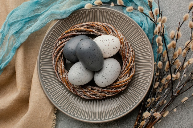 Вид сверху цветных пасхальных яиц в корзине на тарелке с цветами