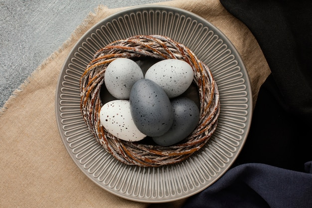 Вид сверху цветных пасхальных яиц в корзине на тарелке