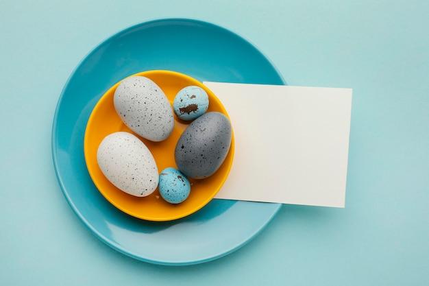 Вид сверху цветных пасхальных яиц на тарелках с бумагой