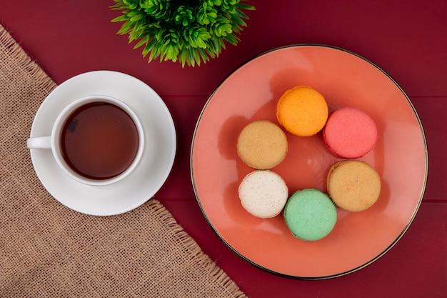 Вид сверху цветных макарон на тарелке с чашкой чая на красной поверхности
