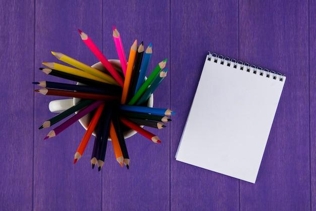 Вид сверху цветные карандаши в чашку и блокнот на фиолетовом фоне