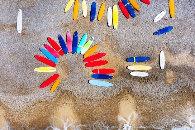 프랑스의 조약돌 해변에 혼란스럽게 누워있는 컬러 서핑 보드의 상위 뷰.