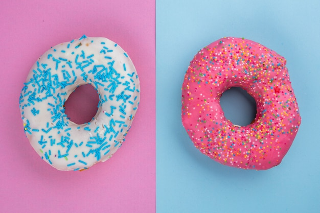 Вид сверху разноцветных сладких пончиков на светло-сине-розовой поверхности