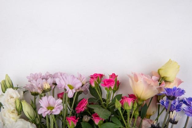 スペースと白い背景の上のバラやデイジーの花などのカラフルで素晴らしい花の上面図