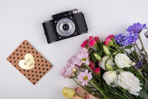 白い背景の上のカメラとバラやデイジーの花などのカラフルで素晴らしい花の上面図
