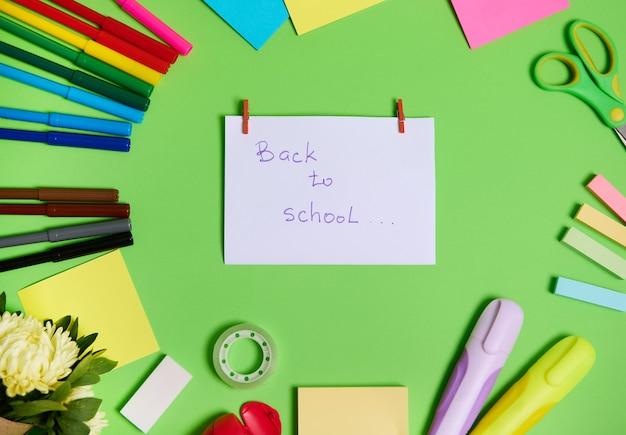 Вид сверху красочного ассортимента канцелярских принадлежностей и школьных принадлежностей, расположенных по кругу, с белой бумагой в центре с надписью «снова в школу». зеленый фон, копией пространства
