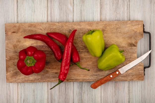 Вид сверху разноцветных перцев колокола и чили на деревянной кухонной доске с ножом на серой деревянной поверхности