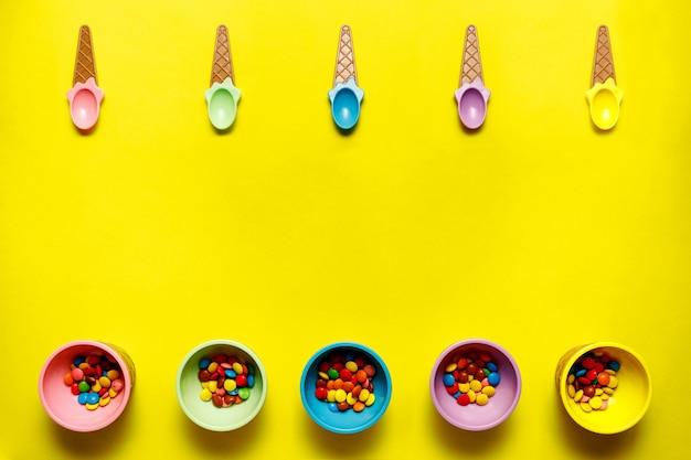 Вид сверху красочных конфет в цветных мисках на желтом фоне.