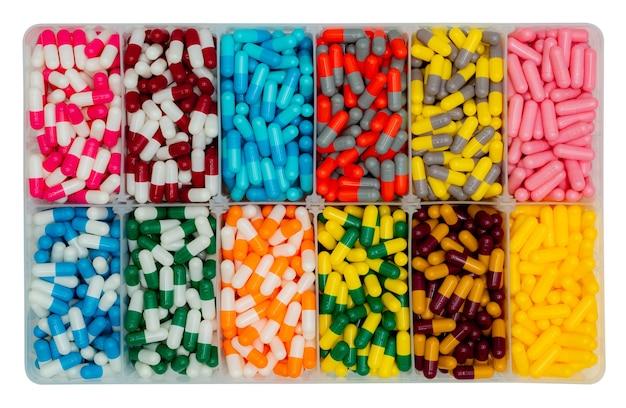 プラスチックの箱に入ったカラフルなカプセルピルの上面図。抗生物質、鎮痛薬、ビタミン、サプリメントのカプセルピル。