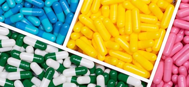 プラスチックの箱の中のカラフルなカプセルの丸薬の上面図。トレイのピンク、黄色、青、緑白のカプセル錠剤。薬局のウェブバナー。製薬業界。ヘルスケアの背景。オンライン薬局のコンセプト。