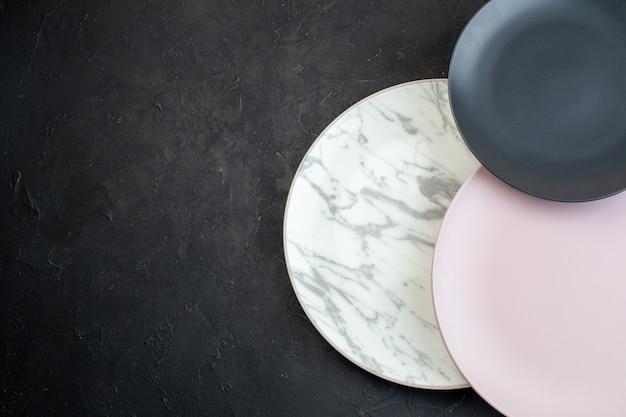 Вид сверху красочных керамических пустых тарелок на черном фоне со свободным пространством