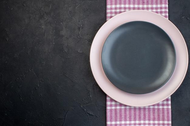 Вид сверху на красочные керамические пустые тарелки на розовом полосатом полотенце на черном фоне со свободным пространством