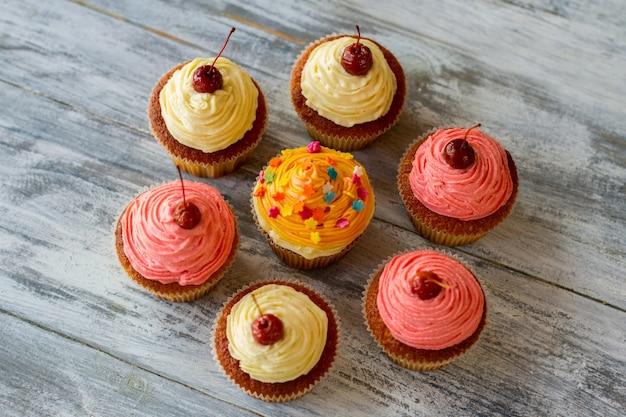 회색 나무 표면에 있는 다채로운 컵케이크 디저트의 꼭대기 전망은 아이싱을 곁들인 맛있는 패스트리입니다.