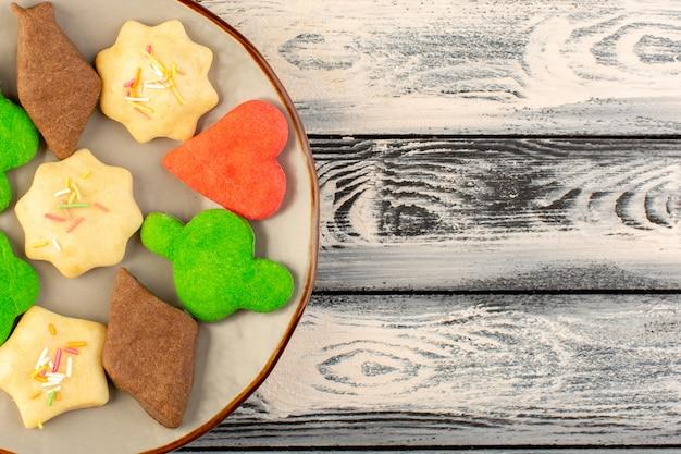 灰色のデスククッキービスケット甘い砂糖茶の丸皿の中に形成された異なるカラフルなおいしいクッキーのトップビュー