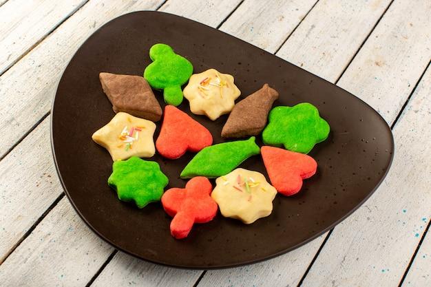 Взгляд сверху красочных вкусных печений различных сформированных пестротканых внутри темной плиты