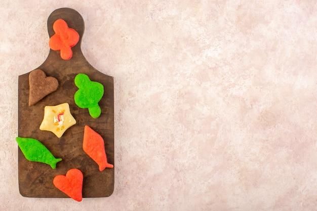 茶色の木製の机の上に形成された異なるカラフルなおいしいクッキーのトップビュー