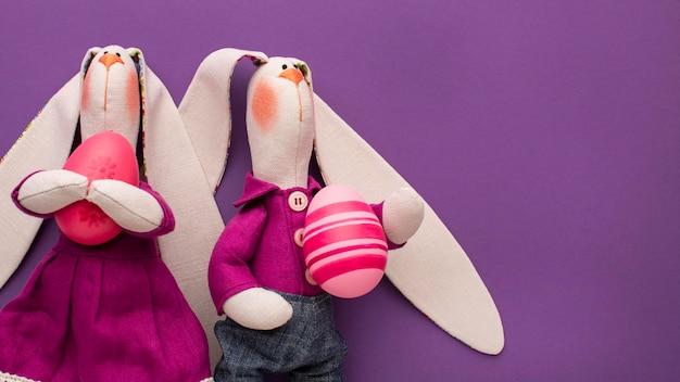 Вид сверху на красочные пасхальные яйца в руках игрушечных кроликов
