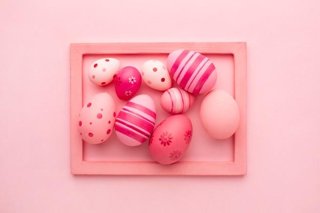 Вид сверху красочные пасхальные яйца в рамке