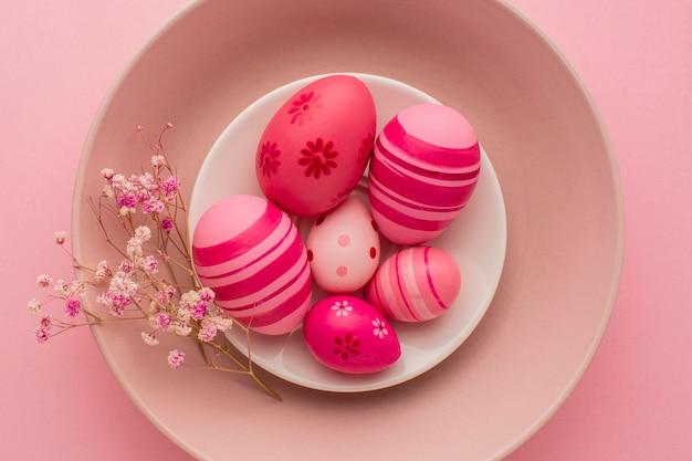 Вид сверху красочные пасхальные яйца на тарелке с цветами