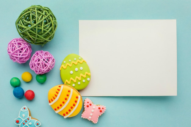 Вид сверху красочные пасхальные яйца с бабочкой и бумагой
