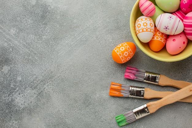 Вид сверху на красочные пасхальные яйца с кистями и копией пространства