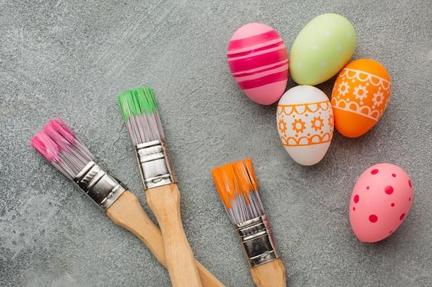 Вид сверху красочных пасхальных яиц с кистями