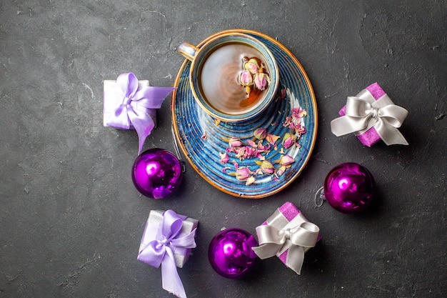 Вид сверху красочных подарков и украшений с чашкой черного чая на темном фоне