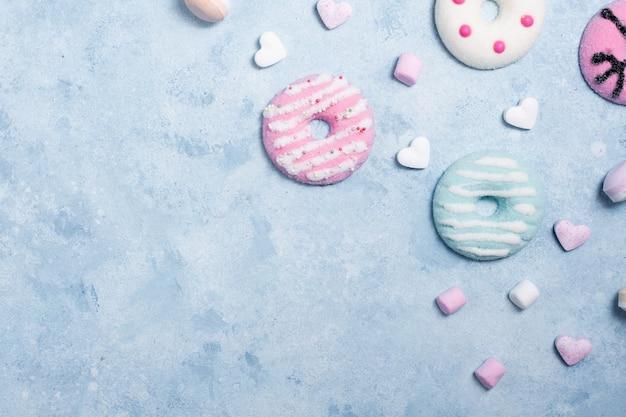 Вид сверху красочные глазированные пончики с зефиром и конфеты
